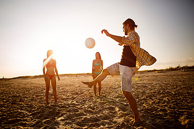Friends playing soccer at beach against sky - p1166m1096308f by Cavan Images