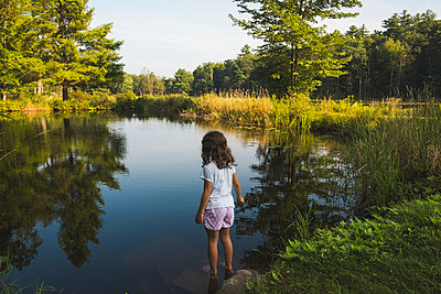 Rear view of girl standing at lakeshore in forest - p1166m2034628 by Cavan Images