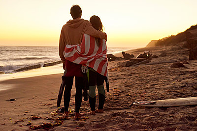 Couple embracing on the beach at sunset next to surfboard - p300m1205802 by Fotoagentur