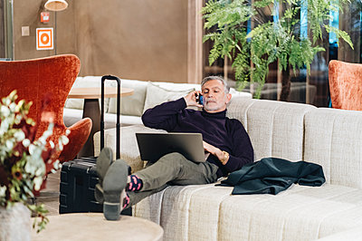 Businessman talking on mobile phone while resting on sofa with laptop at hotel - p300m2273948 by Daniel González