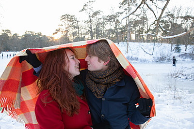 Happy girlfriend with boyfriend under blanket during winter - p300m2287413 by Frank van Delft
