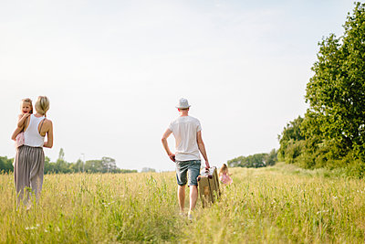 Family walking in meadow - p312m1229303 by Lisa Wikstrand