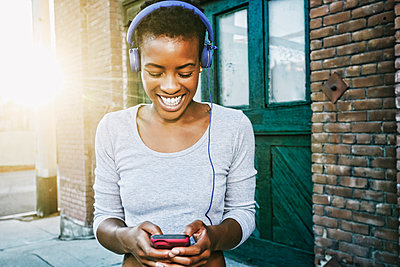 Smiling Black woman listening to cell phone with headphones in city - p555m1444201 by Peathegee Inc