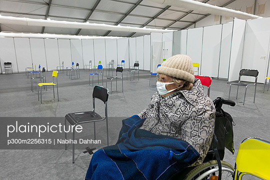 Senior women wearing protective face mask and warm clothing sitting on wheelchair at vaccination center - p300m2256315 by Nabiha Dahhan
