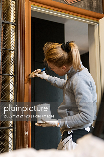 Painter painting door frame in apartment building - p352m2121428 by Folio Images