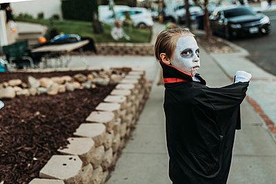 School aged boy dressed as Dracula Trick-or-Treating during Halloween - p1166m2208381 by Cavan Images