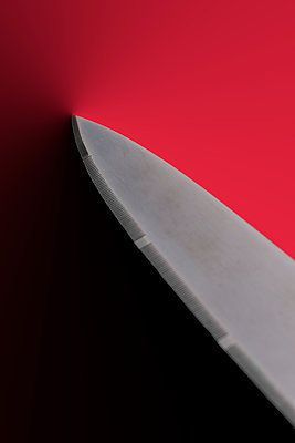 Sharp knife against a red background - p1228m2125856 by Benjamin Harte