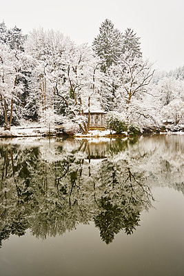 Pavillion on the lake with snow-capped trees - p1312m2182157 by Axel Killian
