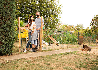 Portrait of confident family standing at chickenhouse in garden - p300m2083772 by Michelle Fraikin