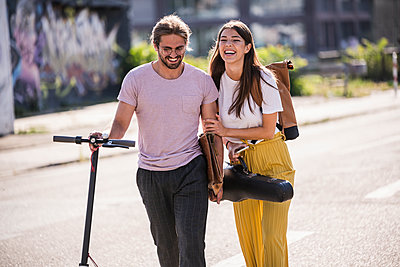 Happy young couple with electric scooter walking on the street - p300m2132534 by Uwe Umstätter