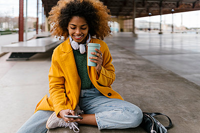 Smiling Afro woman with disposable coffee cup using mobile phone in sitting area - p300m2265818 by Ezequiel Giménez