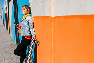 Thoughtful young woman with mobile phone looking away while leaning on wall by longboard - p300m2274409 by Ezequiel Giménez