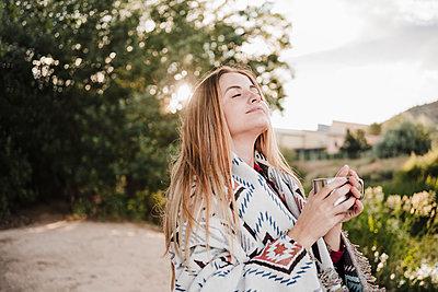woman wrapped on plaid holding mug of coffee, Madrid, Spain - p300m2290487 von Eva Blanco