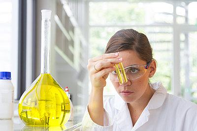 Portrait of young female chemist holding glass tube with yellow reagent - p300m950695f by Sigrid Gombert