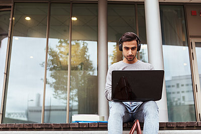 Low angle view of university student wearing headphones while using laptop against glass window at campus - p426m2072275 by Kentaroo Tryman