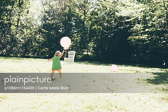 Kind spielt mit einem Luftballon im Garten - p1086m1154439 von Carrie Marie Burr