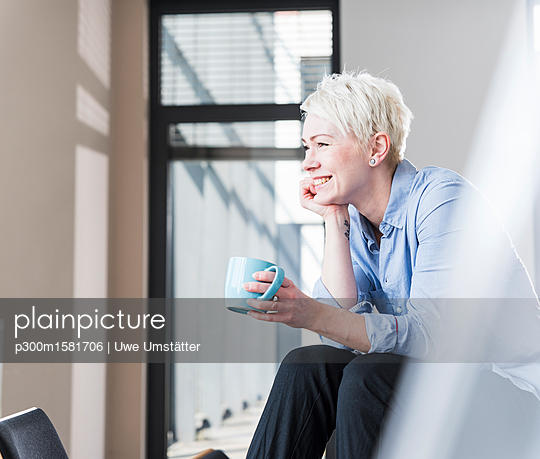 Smiling woman with cup of coffee sitting on table in office - p300m1581706 von Uwe Umstätter
