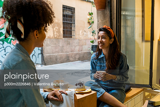 Friends smiling while having food and drink sitting at cafe - p300m2226846 by Valentina Barreto