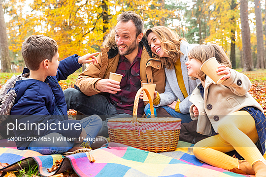 Family enjoying having coffee while sitting together in forest - p300m2257455 by William Perugini