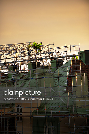 Construction workers on scaffolding at sunset - p352m2119105 by Christofer Dracke