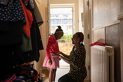Mother helping daughter with jacket at front doorway - p1023m2238494 by Himalayan Pics