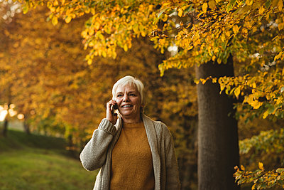 Smiling senior woman taking on phone in the park during dawn - p1315m1565666 by Wavebreak