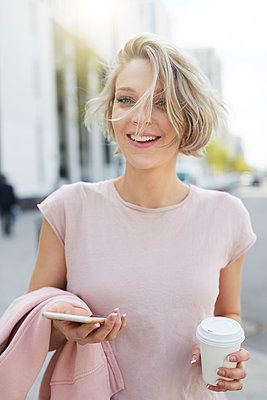 Portrait of happy blond woman with takeaway coffee and cell phone in the city - p300m2012927 von Philipp Nemenz