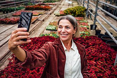 Smiling female farmer taking selfie through smart phone in plant nursery - p300m2300548 by Vasily Pindyurin