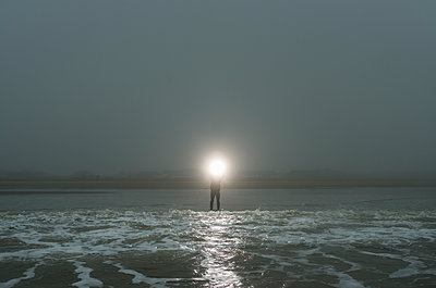 Person standing in tide, shining light out to sea - p429m1227362 by Mischa Keijser