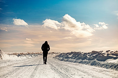 Caucasian man walking in snowy landscape - p555m1312241 by Vladimir Serov