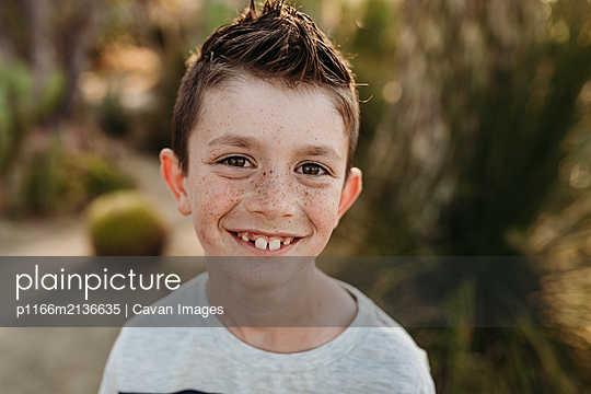 Close up portrait of cute young boy with freckles smiling - p1166m2136635 by Cavan Images