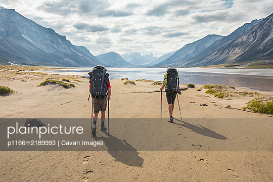 Rear view of two backpackers hiking, leaving footprints in the sand. - p1166m2189993 by Cavan Images