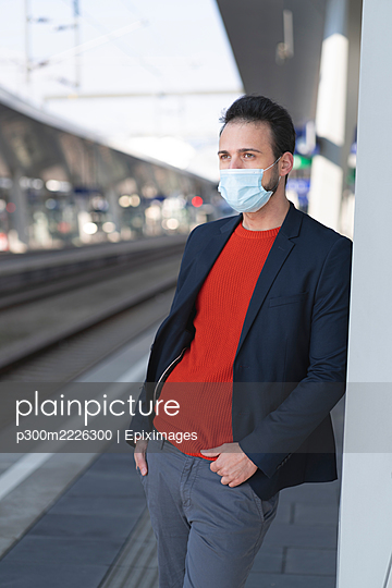 Male entrepreneur wearing protective mask while looking away on railroad station platform - p300m2226300 by Epiximages