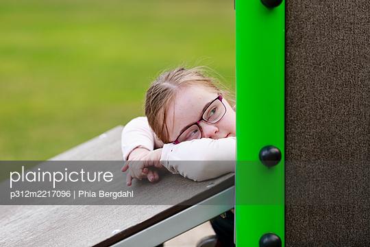 Girl on playground looking away - p312m2217096 by Phia Bergdahl