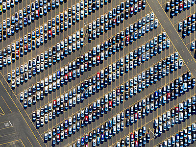 Aerial view of a car distribution centre, new cars parked in rows on a lot ready for sale.   - p1100m1216253 by Mint Images