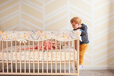 Toddler reaching in crib trying to touch newborn baby's head - p1166m2136718 by Cavan Images