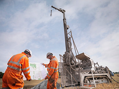 Drilling rig workers inspecting map in field - p429m860144f by Monty Rakusen