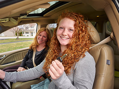 Caucasian teenage girl showing key with mother in car - p555m1412827 by Jeff Greenough