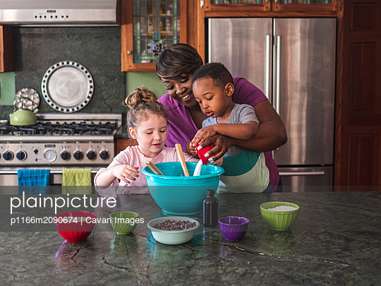 Mother helping children make cookies - p1166m2090674 by Cavan Images