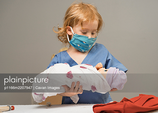 young child wearing medical PPE holds a swaddled baby doll - p1166m2207947 by Cavan Images