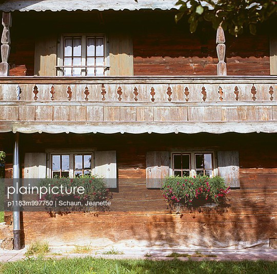 Natural patina of weathered facade with balcony and window boxes of trailing geraniums - p1183m997750 by Schaun, Jeanette