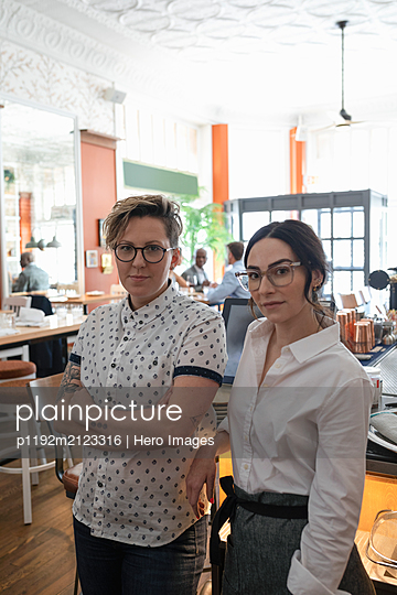 Portrait of restaurant owner and waitress looking at camera - p1192m2123316 by Hero Images