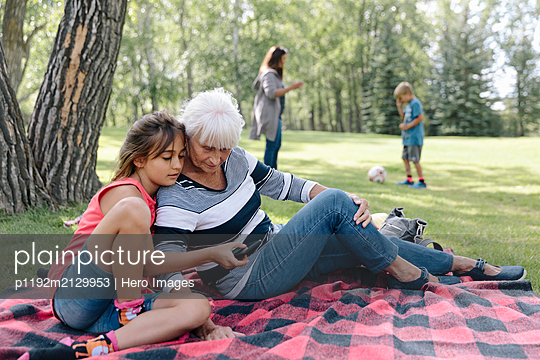Granddaughter showing grandmother smartphone on picnic rug - p1192m2129953 by Hero Images
