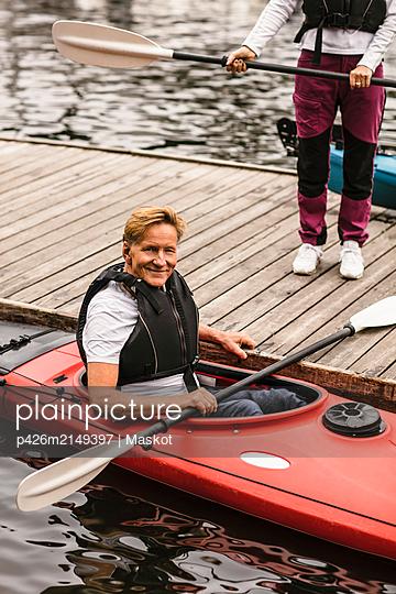 Portrait of smiling senior man sitting in kayak during kayaking course - p426m2149397 by Maskot