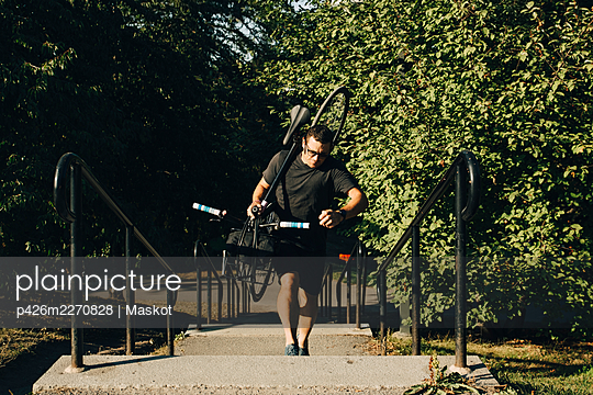 Active male athlete climbing steps while carrying bicycle in park - p426m2270828 by Maskot