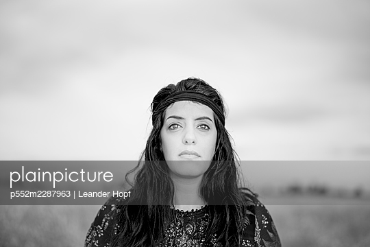 Portrait of black-haired woman with headband - p552m2287963 by Leander Hopf