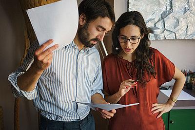 Businessman and businesswoman reviewing paperwork in office - p301m2039641 by Halfdark