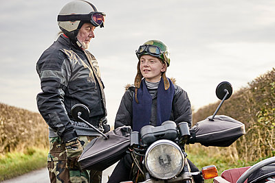 Senior male motorcyclist talking to grandson sitting on motorcycle - p429m1227256 by GS Visuals