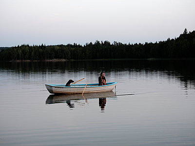 Woman and dog in a rowing boat - p551m2056708 by Kai Peters