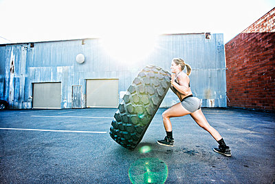 Caucasian woman working out with heavy tire outdoors - p555m1304126 by Peathegee Inc
